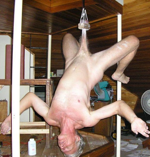 Old naked guy hanging from the ceiling by his balls